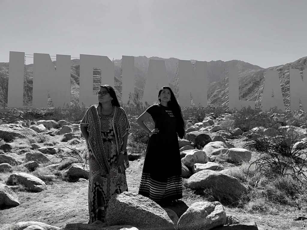 """Eunique Yazzie and Melody Lewis stand in front of Nicholas Galanin's mountaintop art installation, """"Never Forget,"""" which depicts a Hollywood-esque sign with the word Indianland."""