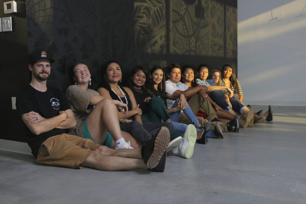 A group photo of Cahokia's members and community ambassadors sitting on the floor in front of the space's entrance mural.