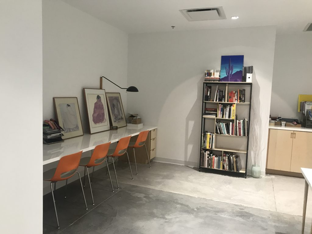 A room with a workspace set up against the wall, a bookshelf, and a counter. Surfaces have paintings and prints resting on them.